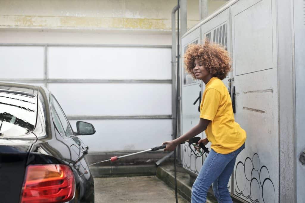 girl washing a black car
